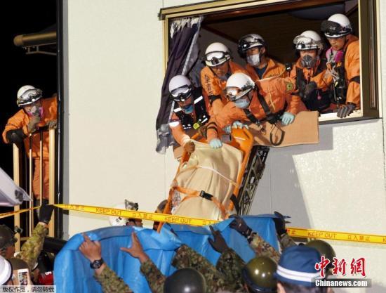 救援人员用担架将一名在地震中受伤的女性抬出危楼。